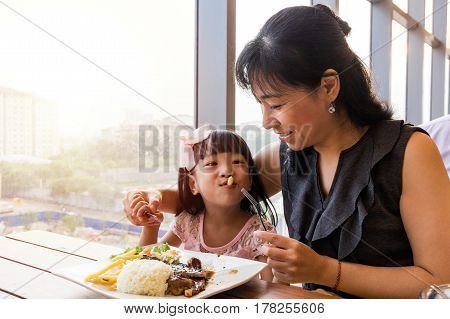 Asian Chinese Mother And Daughter Eating Steak