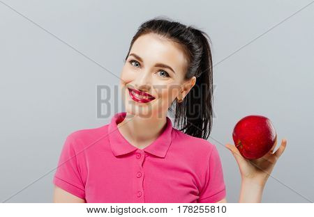 Young beautiful sexy girl with dark hair, holding big red apple