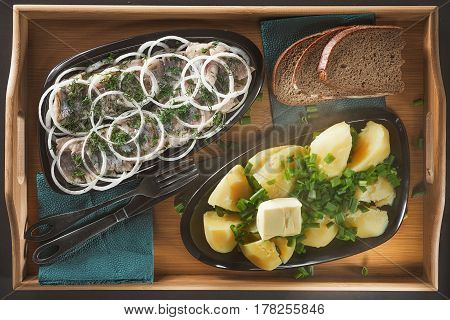 Pieces of a herring with rings of onions and fennel, hot boiled potatoes with green onions and a piece of butter on two black ceramic plates of an ovoidny form on a wooden tray from a bamboo