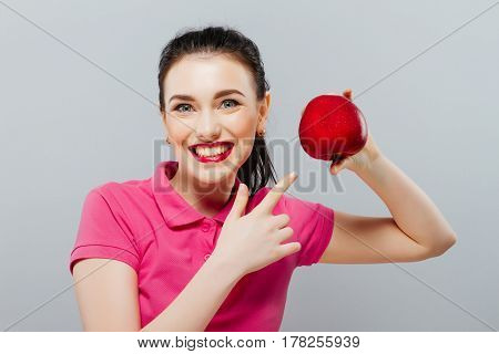Young beautiful sexy girl with dark hair, holding big red apple to enjoy the taste and are dieting, healthy eating and organic foods, feeling temptation, smile, teeth