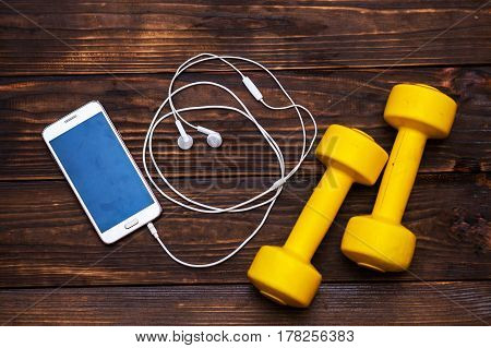 Blank Moblie smart phone with ear phone and dumbbells on wood healthy life style concept top view and free space for text