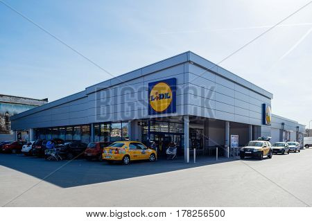 BUCHAREST ROMANIA - MAR 24 2016: Lidl supermerket entrance with trolleys cars in parking and customers going to supermarket for shopping