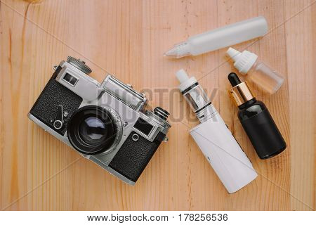 Modern Electronic Mech Mod Vaping Device. Electronic Cigarette And Photo Camera On A Wooden Backgrou