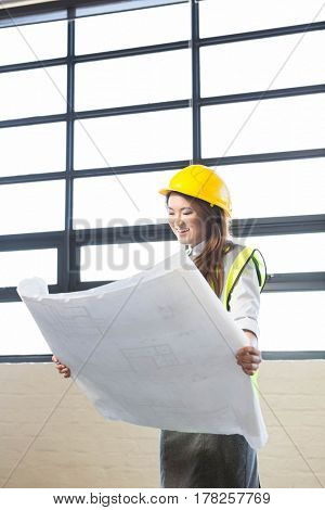Architect looking at blueprint in office