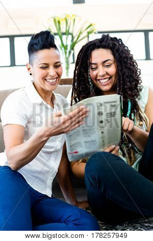 Lesbian couple smiling while reading newspaper