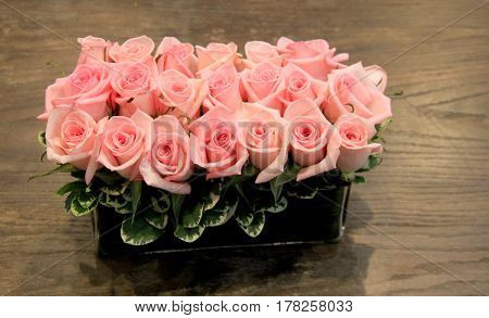 Beautiful image in long, rectangular vase filled with several pink roses