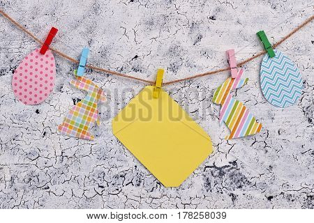 Easter paper cutouts and clothespins. Blank card on rope.