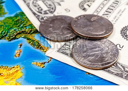 Coins with US dollars banknotes on the background of geographic map. Travel concept
