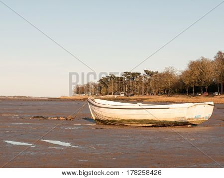 A boat standing stationary in the in mud with the tide out