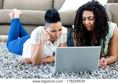 Smiling lesbian couple lying on rug and using laptop in living room