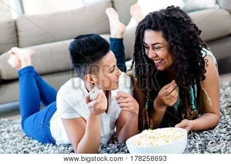 Lesbian couple lying on rug with a bowl of popcorn and remote control