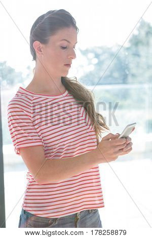angry woman standing inside a window reading her mobile phone