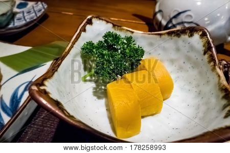 Yellow daikon radish and fresh parsley sprig in a ceramic dish - a typical part of a Japanese meal. Image captured under available light condition.