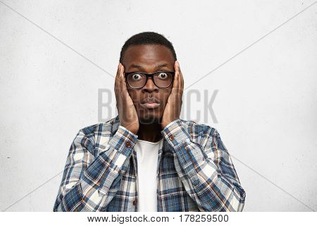 Human Emotions And Facial Expressions. African Man Model In Glasses, Dressed Casually, Posing For Po