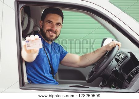 Delivery man sitting in his van while showing his driving licence
