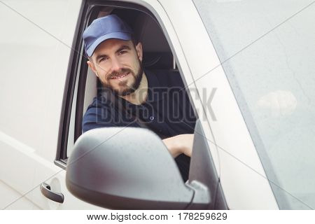 Delivery man sitting in his van while looking at camera