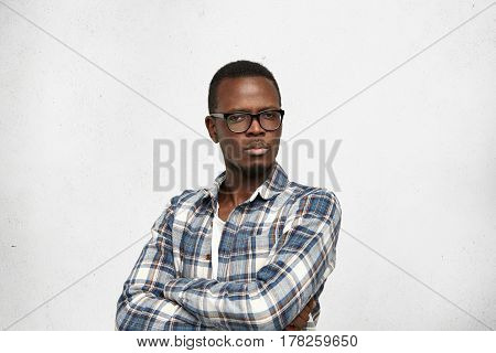 Studio Shot Of Sceptical Suspicious Young African Man Standing At White Wall, Keeping Arms Crossed,