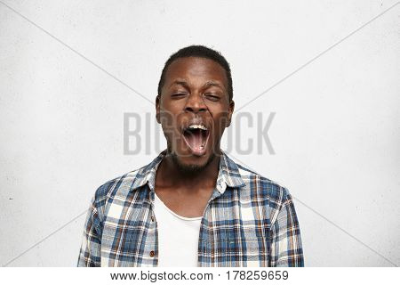 Headshot Of Young Bored Black Man, Yawning Isolated On Light Background. Facial Expressions, Feeling