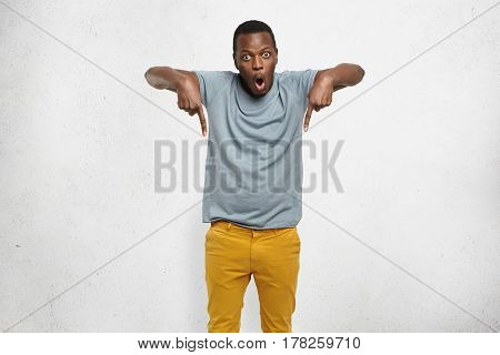 Check This Out! Cropped Studio Shot Of Attractive Excited Young African Male In T-shirt And Mustard