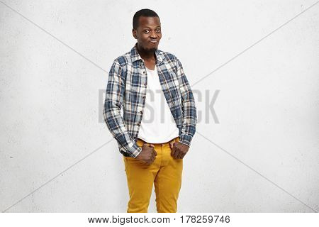 Confused Frustrated Dark-skinned Male Wearing Mustard Pants And Checkered Shirt Over White T-shirt,