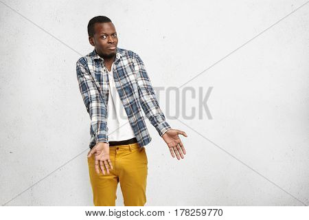 Indignant Confused African American Male In Checkered Shirt And Mustard Pants Shrugging Shoulders, S