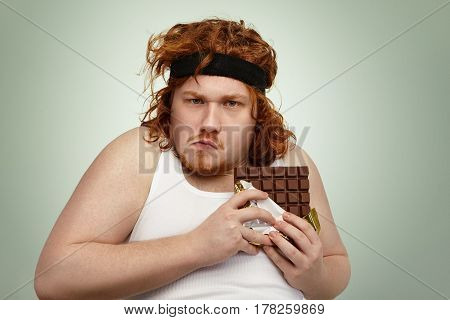 Greedy Obese Fat Young Man Wearing Sports Band On Curly Ginger Hair, Grimacing, Looking At Camera Wi