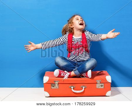 Child blonde girl with pink vintage suitcase ready for summer vacation. Travel and adventure concept.