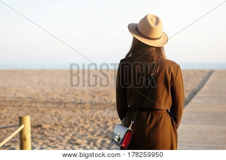 Unrecognizable Young Female Wearing Stylish Hat, Coat And Shoulder Bag Contemplating Amazing View Of