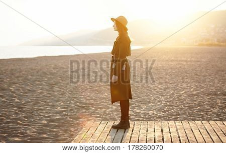 Outdoor Shot Of Fashionable Female Wearing Stylish Overclothes Standing On Wooden Boardwalk In The M
