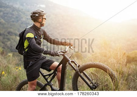 Side View Of Young Stylish Male Biker In Black Sportswear Standing On Top Of Hill With His Electric