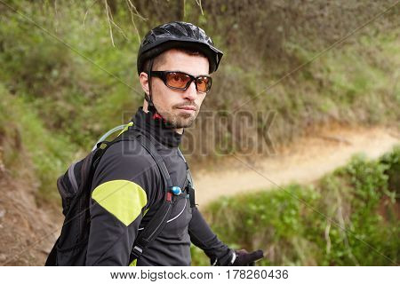Portrait Of Handsome Confident Professional Cyclist In Sportswear, Glasses, Helmet And Backpack Look