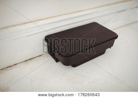 Rat bait box on white floor in a home