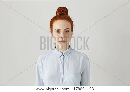 Studio Portrait Of Beautiful Young Redhead Female Employee With Hair Bun Posing Indoors Dressed In L