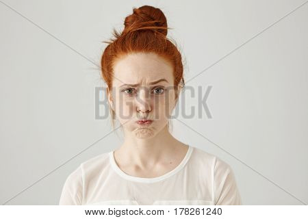 Headshot Of Attractive Funny Young Female With Ginger Hair Dressed In White Blouse Feeling Displease