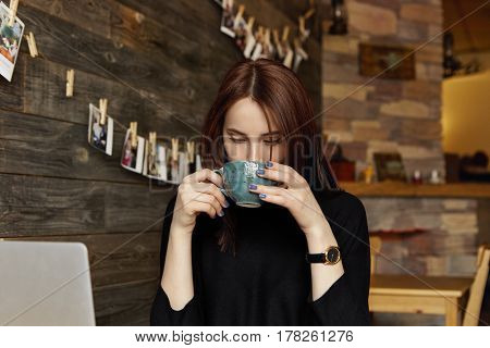 Candid Shot Of Beautiful Brunette Woman Freelancer In Black Clothing Drinking Coffee Or Tea Out Of L