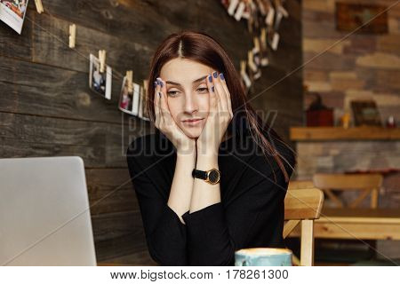 Stressed Young Caucasian Female Freelancer Resting Face On Her Hands Looking At Laptop Screen In Fro