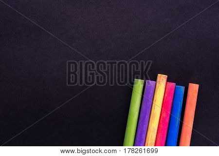 Multicoloured chalk on blackboard background, business concept