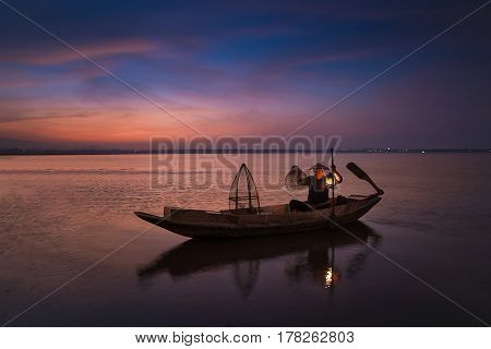 Asian Fisherman On Wooden Boat In Nature River At The Early Morning Before Sunrise