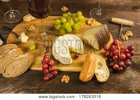 A photo of a cheese selection at a tasting, with bread, purple and white grapes, walnuts, and wine glasses