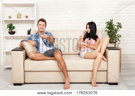 Dissapointed beautiful brunette woman in quarrel with her boyfriend. Indifferent man watching TV at home.