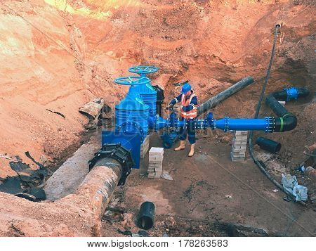 Main City Water Supply Pipeline. Technical Staff In Reflective Vest Underground