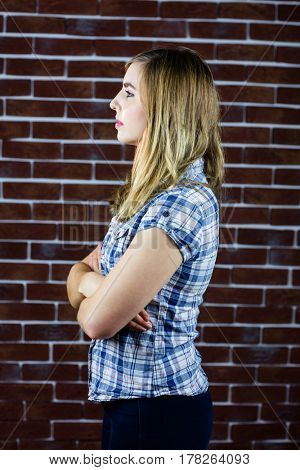 Pretty blonde woman day dreaming on brick wall background