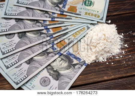 Cocaine drug powder and dollar bills on a wooden background