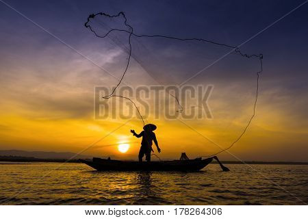 Asian fisherman on wooden boat throwing a net for catching freshwater fish in nature river in the early morning before sunrise