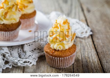 Caramel cupcakes with buttercream frosting on rustic wood