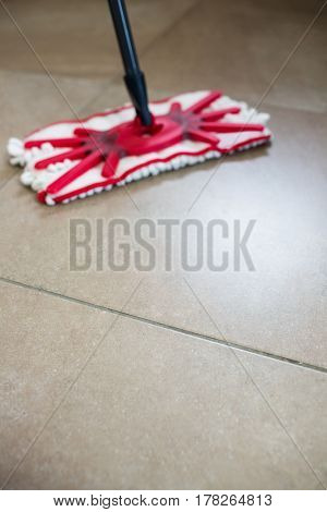 View of a mop swiping the kitchen floor