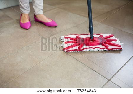 Woman swiping the kitchen floor with a mop