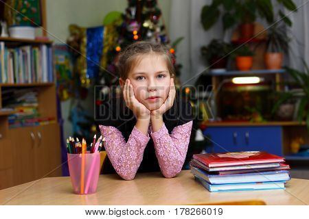 The girl is sitting at a school desk and is bored. The girl is depressed at school