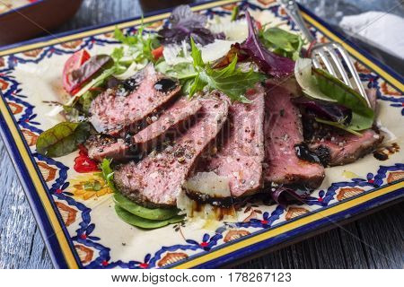 Traditional Italian Tagliata di Manzo Steak with Parmesan and Salad as close-up on a plate