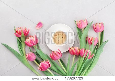 Cup of coffee with spring tulip flowers for good morning on gray stone table top view in flat lay style. Breakfast on Mothers or Womens day.